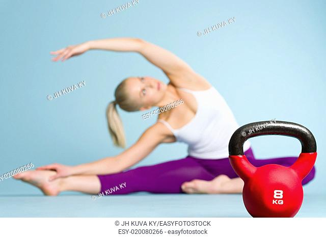 Fitness girl stretching and focus on the kettlebell front of her, horizon format