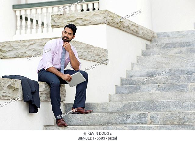 Indian businessman using digital tablet on steps