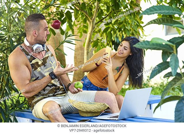 young woman using smartphone to take photo of muscular man throwing apple in the air, while sitting on bench in nature. With headphones and laptop