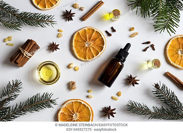 Selection of essential oils with Christmas spices and ingredients on white background: bottles of essential oil, spruce, fir, frankincense resin, star anise