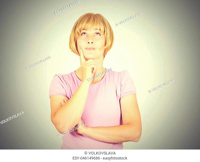 Portrait of a young Thinking blonde girl. Woman thinks looking up a person's hand. Isolated on background