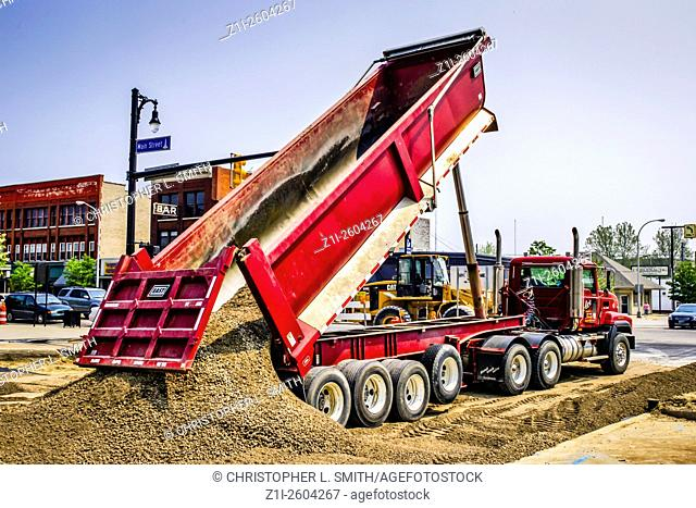 A large tipper truck unloads sand at a repaving project in downtown Port Huron Michigan MI