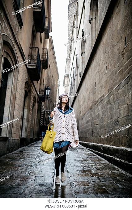 Spain, Barcelona, young woman walking in an alley