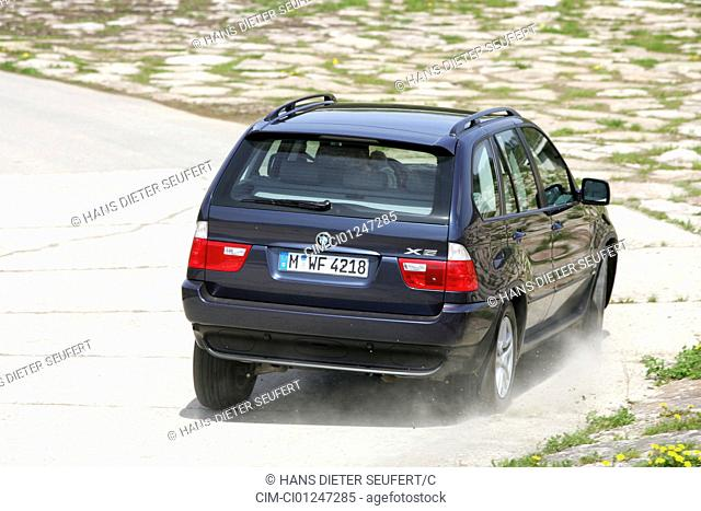 Car, BMW X5 3.0d, model year 2005-, black, cross country vehicle, driving, diagonal from the back, rear view