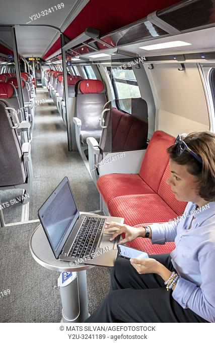 Business Woman Working on Laptop and Smartphone in First Class in a Train in Switzerland