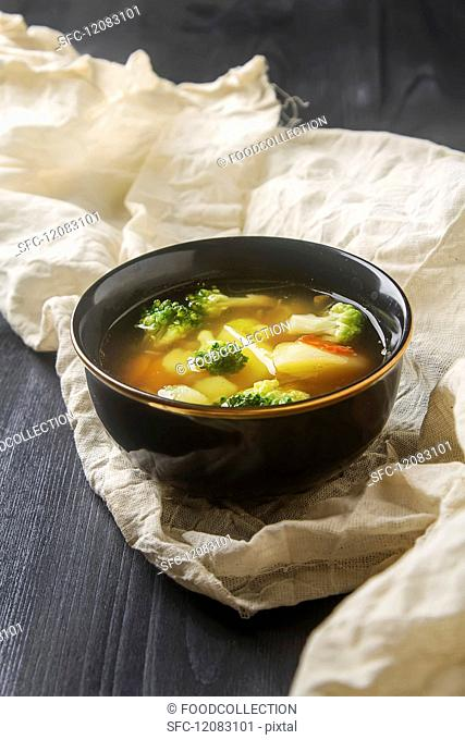 A vegetarian soup with cauliflower, broccoli and carrots