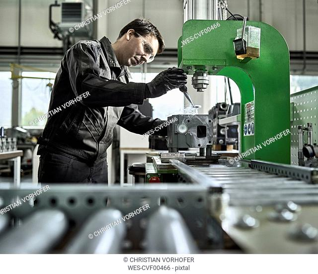 Worker in metalworking factory loading cylinder head
