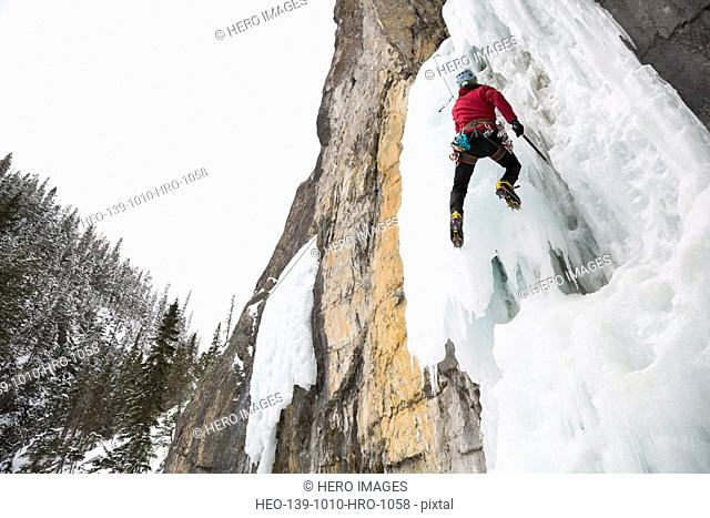 Low angle view of man climbing ice wall in mountains