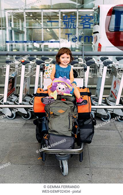 Baby girl sitting on the top of the luggage in a trolley at the airport