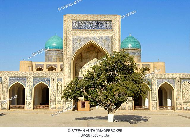 Tree in front of rich decorated iwan inside Mosque Kalon Bukhara Uzbekistan