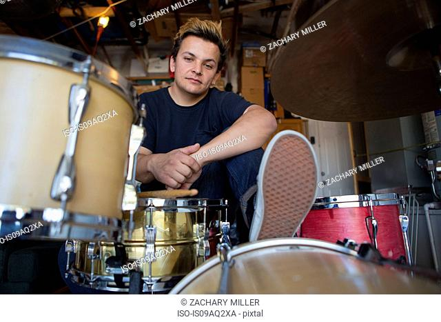 Portrait of young male drummer in basement