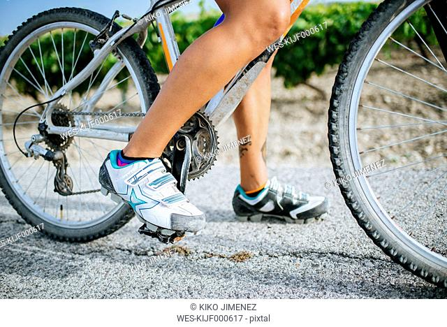Close-up legs of female cyclist with cycling shoes