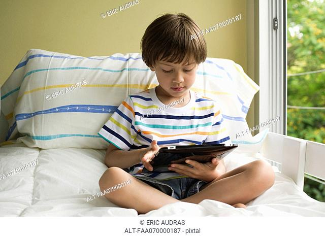 Boy sitting on bed, using digital tablet