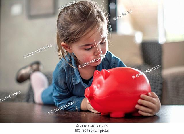 Girl lying on coffee table gazing at red piggy bank