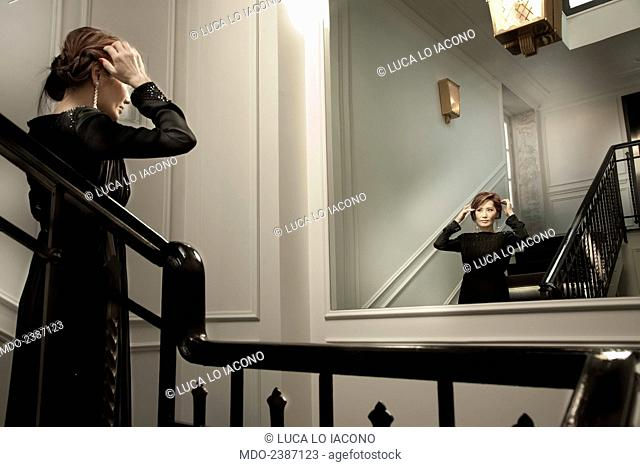 The beautiful Chinese Canadian actress and soprano Lu Ye looking at herself in the mirror on the stairs in an elegant dress designed by Giorgio Armani for the...