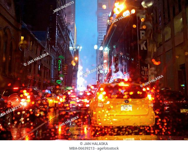 Rain drops on car's windshield are illuminated red by taxicab brake lights