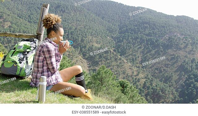 Young woman sitting ground and drinking