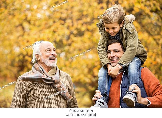 Three generations of men smiling in park