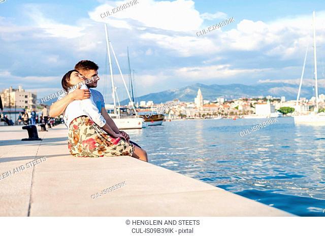 Young couple sitting on harbour, Split, Dalmatia, Croatia