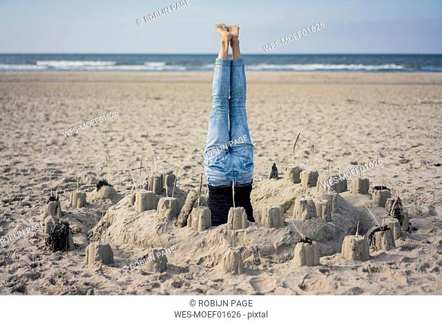 Mature woman doing a headstand on the beach in a sandcastle