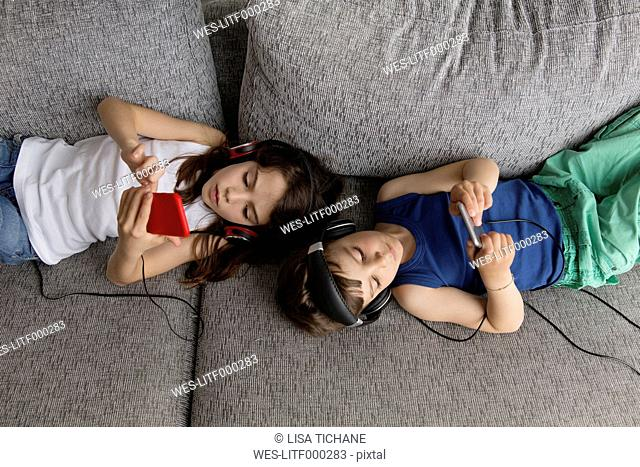 Siblings lying on the couch listening music with their headphones and smartphones