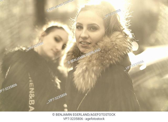 Two young sisters in sunlight, wearing winter clothing, in Munich, Germany