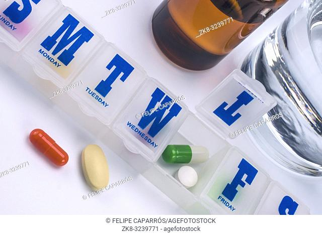 weekly pillbox with medication, conceptual image, horizontal composition