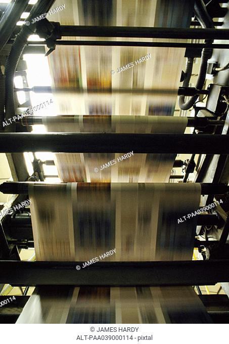 Printed newspaper on printing press, blurred motion
