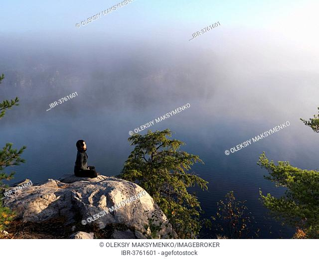Young woman meditating, sitting on a rock with a mist covered lake at background, during sunrise, Killarney, Ontario Province, Canada