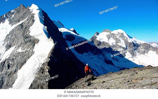 A mountain climber on the summit of a high alpine peak with the Bianco Ridge and Piz Bernina behind