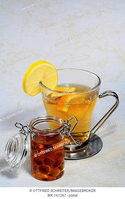 A cup of tea with orange and lemon slices and a lockable glas of rock candy in rum