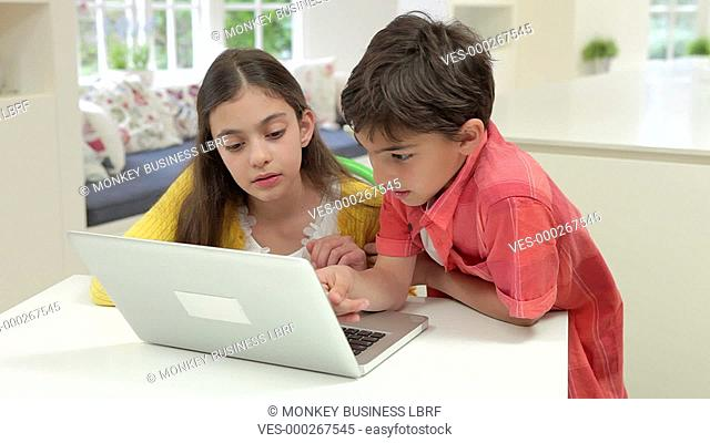 Boy and girl using laptop at home together.Shot on Canon 5d Mk2 with a frame rate of 25fps