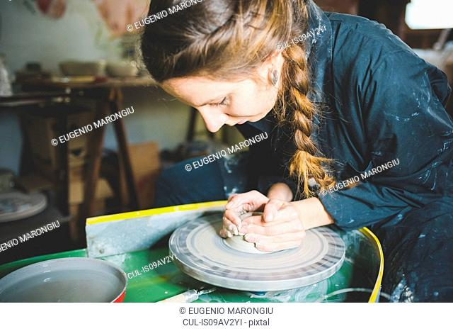 Young woman with plaited hair using pottery wheel