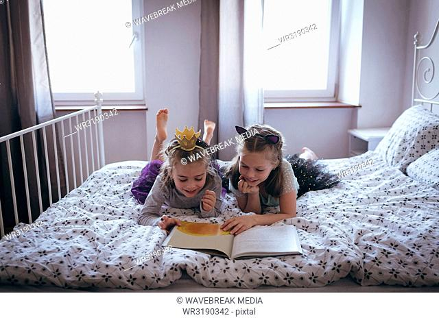 Sisters reading a book on bed