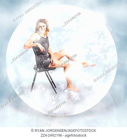 Creative fine art picture of a cute woman sitting inside a glass crystal ball under a seasonal fall of snow flakes. Snow globe pin up girl
