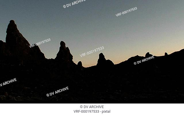 The Trona Pinnacles are silhouetted against the dawn