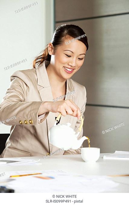 Businesswoman pouring tea