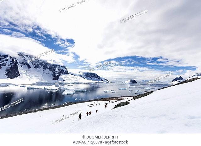 Visitors to Danco Island hike up a snowfield against a backdrop of icebergs and glaciers. Danco Island, Antarctic Peninsula, Antarctica
