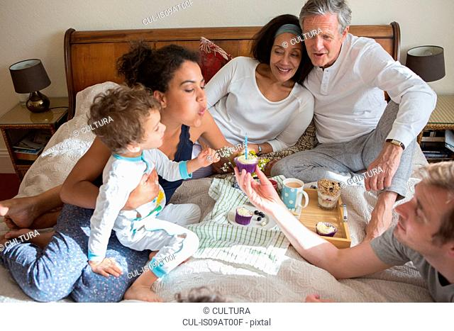 Three generation family sitting on bed, blowing out candle on cupcake