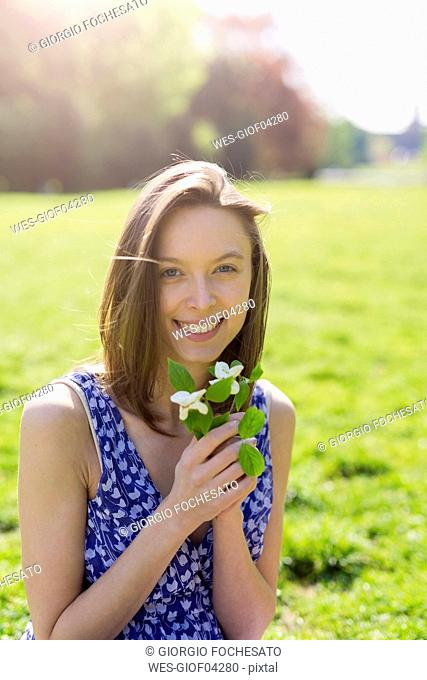 Portrait of smiling young woman in a park holding flowers