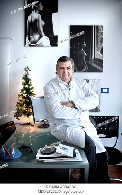 The professor and world famous plastic surgeon Marco Gasparotti posing seated on the desk for a photocall at his medical practice