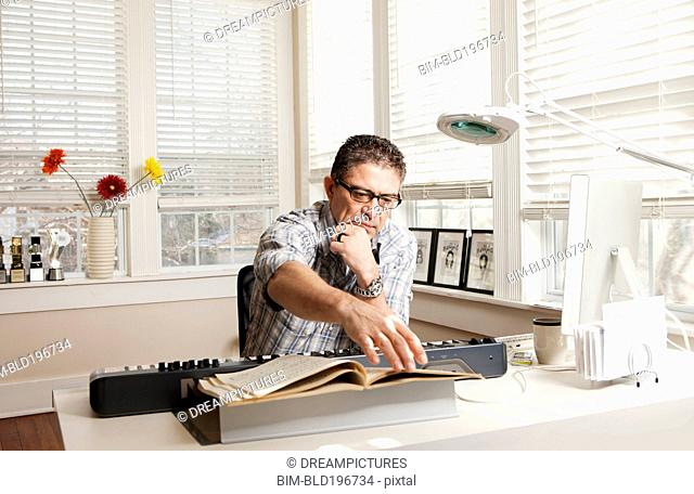 Hispanic man with electronic keyboard and sheet music