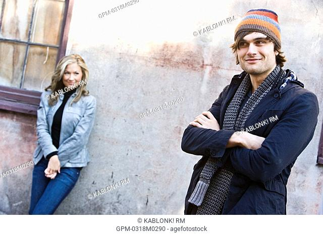 Young couple in warm clothes on street in front of building