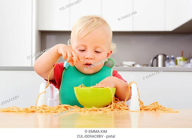 Toddler playing with spaghetti