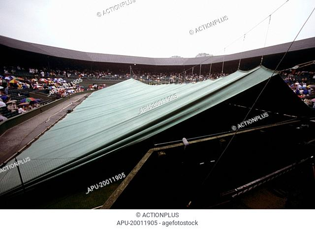 Covers are pulled over court as rain stops play at a tennis tournament