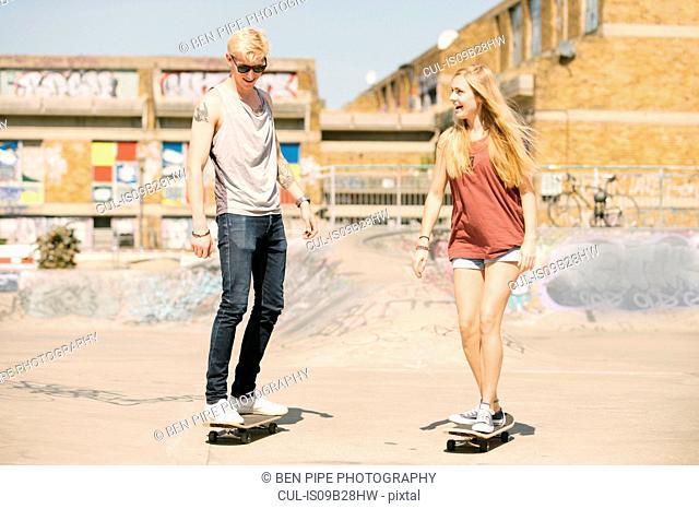 Young female and male skateboarding friends skateboarding in skatepark