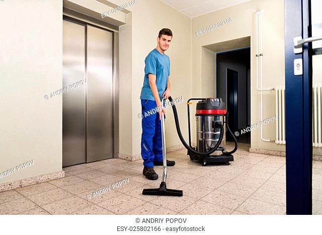 Happy Male Worker Cleaning Floor With Vacuum Cleaner Appliance