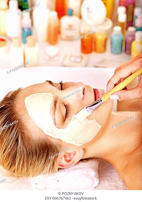 Woman with clay facial mask in beauty spa