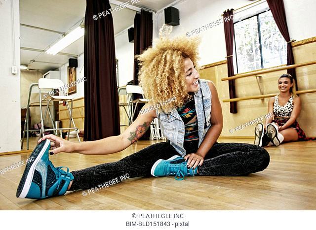 Dancers stretching in studio