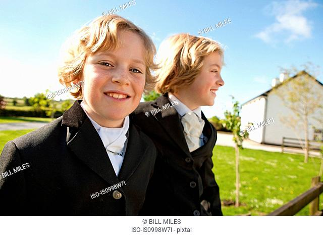 Boys wearing horse riding clothes, smiling